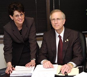 Dr. Suntken, Crystal Clinic's CEO, and Mary Hudec, Odyssey Health Systems' CEO, review quarterly results.